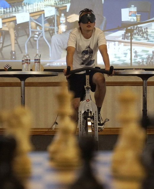 Chess grandmaster Timur Gareyev rides an exercise bike to maintain rhythm and flow during his bid to break the world record for simultaneous chess games played blindfolded at the UNLV Foundations  ...