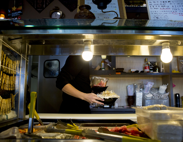 Jason Chan, server at Yunnan Tasty Garden, a restaurant in the Las Vegas Asian Plaza, 5115 Spring Mountain Rd, Las Vegas, sets out food, Friday, Dec. 2, 2016. Elizabeth Page Brumley/Las Vegas Revi ...