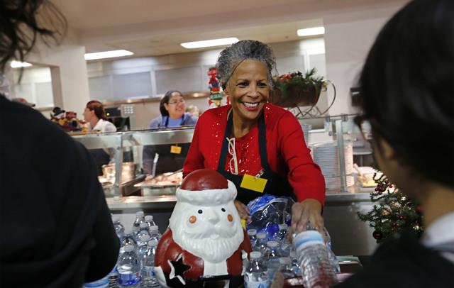 Volunteer Roxanne Givens of Las Vegas serves water bottles during Christmas dinner at Catholic Charities of Southern Nevada in Las Vegas, Sunday, Dec. 25, 2016. Catholic Charities of Southern Neva ...