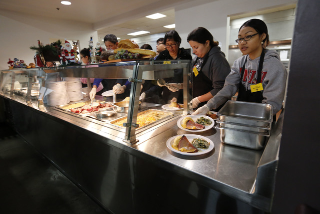 Volunteers serve Christmas dinner at Catholic Charities of Southern Nevada in Las Vegas, Sunday, Dec. 25, 2016. Catholic Charities of Southern Nevada serves Christmas meals to less fortunate peopl ...