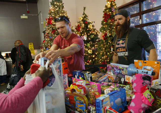 Jeff Reynolds, left, and Mike Skurkis give toys to people who cannot afford to buy gifts to children during Christmas dinner at Catholic Charities of Southern Nevada in Las Vegas, Sunday, Dec. 25, ...