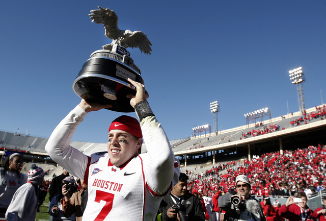 Houston quarterback Case Keenum (7) celebrates with the championship trophy after defeating Penn State in the TicketCity Bowl NCAA college football game, Monday, Jan. 2, 2012, at the Cotton Bowl i ...