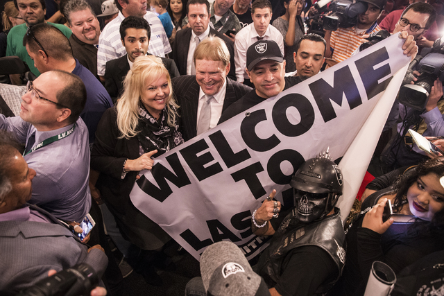 Oakland Raiders owner Mark Davis, middle, celebrates with supporters moments after Gov. Brian Sandoval signed Senate Bill 1 at the Richard TAM Alumni Center at UNLV on Monday, Oct. 17, 2016, in La ...