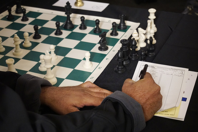 A player records his latest move against Timur Gareyev, a chess grandmaster who broke the world record for simultaneous chess games played blindfolded, at the UNLV Foundations Building in Las Vega ...