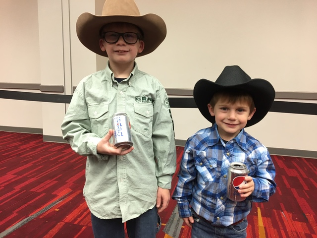 From left, Michael Scattaglia, 8, and brother Thomas, 4, wait patiently while hoping their grandpa, Vito Scattaglia, can score tickets to the Sunday night go-round of the Wrangler National Finals  ...