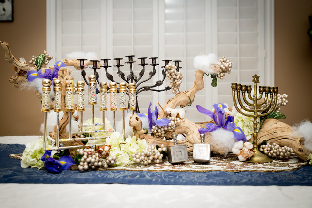 TONYA HARVEY/YOUR HOME Purple and white flowers and a sun-bleached tree branch provide a natural element to this Hanukkah centerpiece.