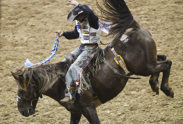 Heith DeMoss rides Going South while competing in the saddle bronc riding event during the 3rd go-round of the National Finals Rodeo at the Thomas & Mack Center in Las Vegas on Saturday, Dec.  ...
