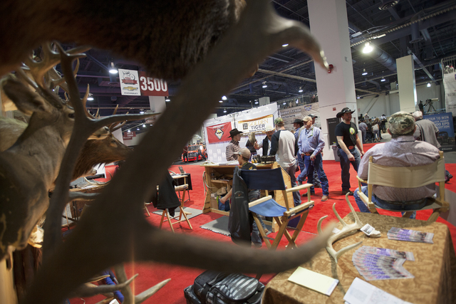 Tony Carricato talks to customers at his booth, Wyoming Guided Hunts, at the Cowboy Christmas gift show in the south halls of the Las Vegas Convention Center on Sunday, Dec. 4, 2016, in Las Vegas. ...