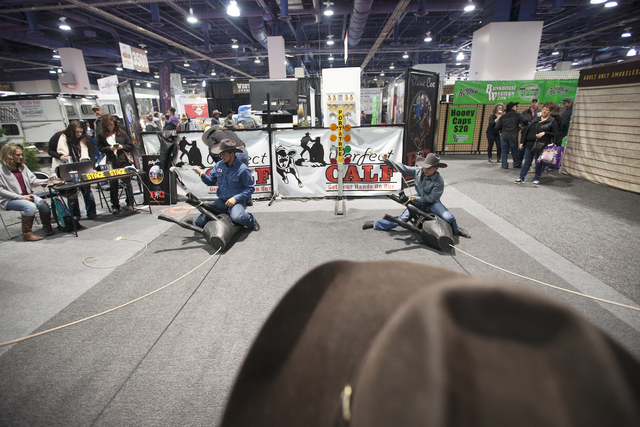 John Michael Elliott, left, and Bryan Rodriguez, 11, compete to tie decoy calfs at the Cowboy Christmas gift show in the south halls of the Las Vegas Convention Center on Sunday, Dec. 4, 2016, in  ...
