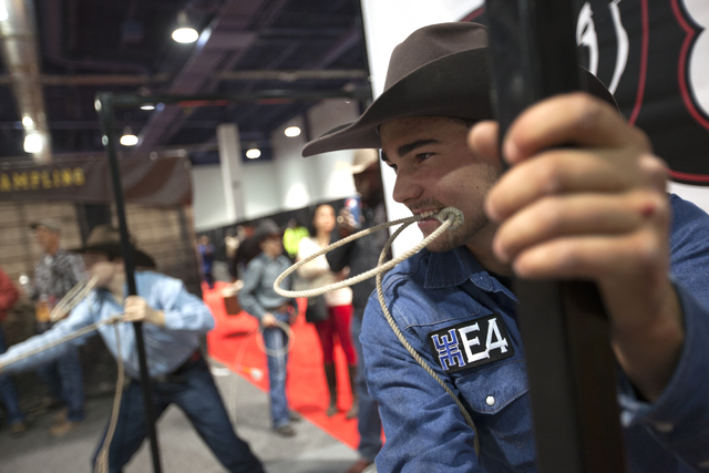 John Michael Elliott, right, prepares to race to tie a decoy calf at the Cowboy Christmas gift show in the south halls of the Las Vegas Convention Center on Sunday, Dec. 4, 2016, in Las Vegas. (Ra ...