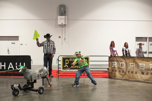 Levi Leathers, 7, ropes a steer at the Three Amigos Super Steer Roping booth as referee and owner Kash Gaikowski watches in the south halls of the Las Vegas Convention Center on Sunday, Dec. 4, 20 ...