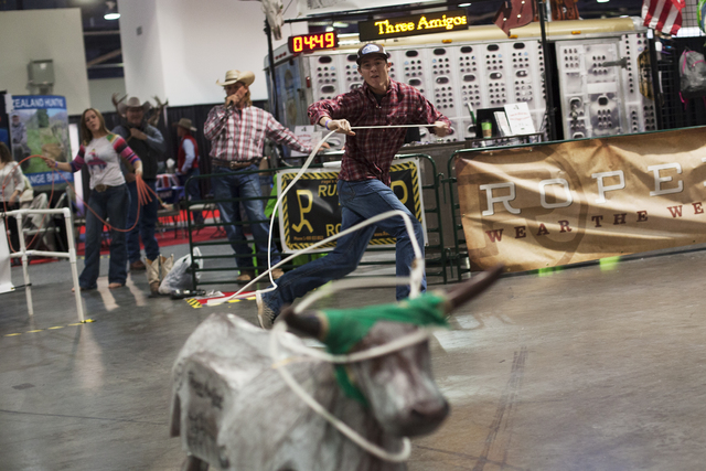Chance Gleave, 18, ropes a decoy steer at the Three Amigos Super Steer Roping booth in the south halls of the Las Vegas Convention Center on Sunday, Dec. 4, 2016, in Las Vegas. (Rachel Aston/Las V ...