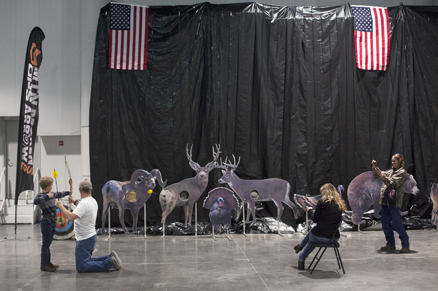 Sean DeGrey, second from left, teaches Eric Hardy, 7, left, to shoot a bow and arrow in the south halls of the Las Vegas Convention Center on Sunday, Dec. 4, 2016, in Las Vegas as his mother Ornel ...