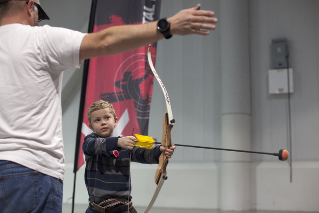 Sean DeGrey teaches Eric Hardy, 7, how to shoot a bow and arrow in the south halls of the Las Vegas Convention Center on Sunday, Dec. 4, 2016, in Las Vegas. (Rachel Aston/Las Vegas Review-Journal) ...