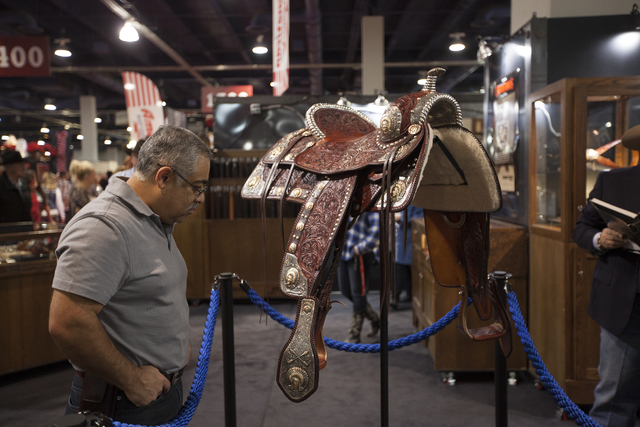 Jorge A. Garcia admires a saddle worth $219,500 and that took 1500 hours to make, in the south halls of the Las Vegas Convention Center on Sunday, Dec. 4, 2016, in Las Vegas. (Rachel Aston/Las Veg ...
