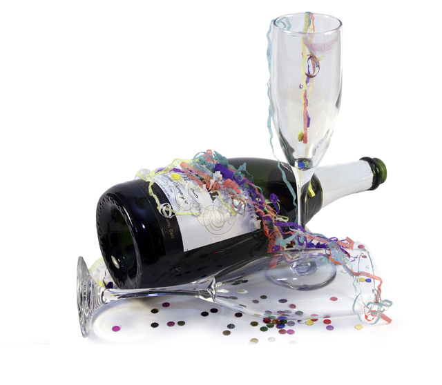 Empty champagne bottle with used glasses confetti and streamers.