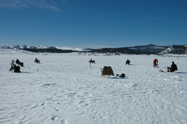 Ice fishing is as much a social acticity as it is a fishig activity. It is common for groups of anglers to drill their fishing holes in proximity to one another. Photo by Doug Nielsen.