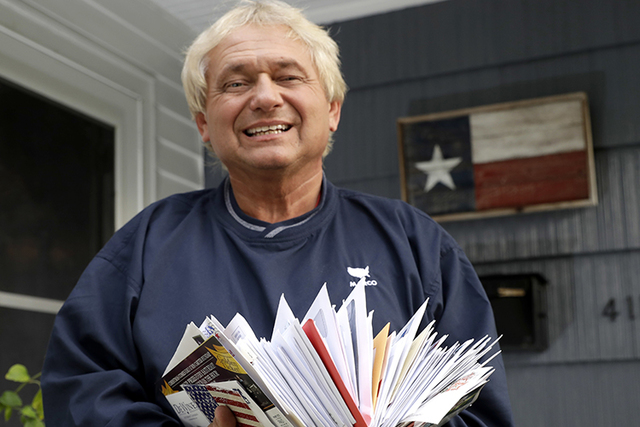 Rex Teter, a member of the Electoral College, holds two days of delivered mail at his home in Pasadena, Texas, last week. Electors are gathering in every state to formally elect Donald Trump presi ...