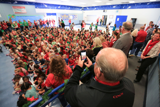 Bob Ellis takes a photo of students as they file into the cafeteria of C.T. Sewell Elementary School in Henderson on Friday, Dec. 16, 2016. The gifts were donated by Bob and Sandy Ellis, who have  ...