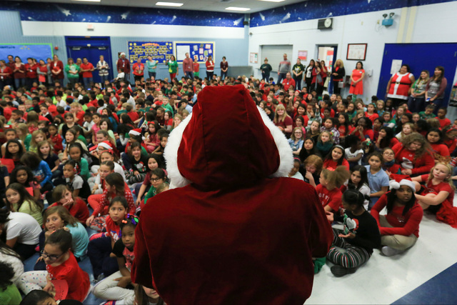 Eric Johnson as Santa talks to students before giving them gifts at C.T. Sewell Elementary School in Henderson on Friday, Dec. 16, 2016. The gifts were donated by Bob and Sandy Ellis, who have don ...