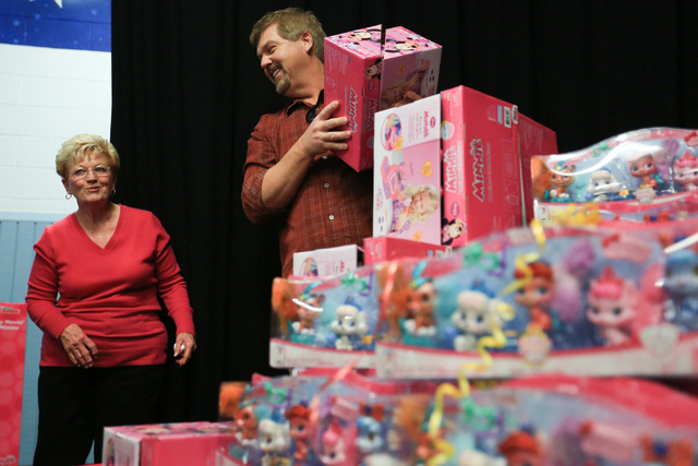 Sandy Ellis, left, and Bob Murnane, Henderson city manager, hand out gifts to students at C.T. Sewell Elementary School in Henderson on Friday, Dec. 16, 2016. The gifts were donated by Bob and San ...