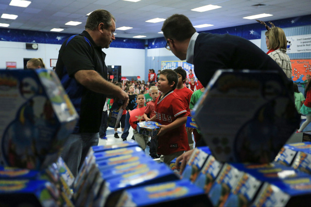 Volunteers hand out gifts to students at C.T. Sewell Elementary School in Henderson on Friday, Dec. 16, 2016. The gifts were donated by Bob and Sandy Ellis, who have donated more than 20,000 shoes ...