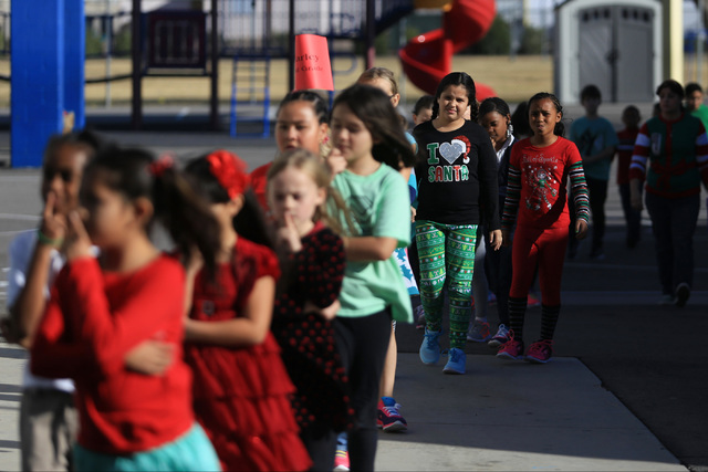 Students line up to enter the cafeteria of C.T. Sewell Elementary School to receive donated gifts in Henderson on Friday, Dec. 16, 2016. The gifts were donated by Bob and Sandy Ellis, who have don ...