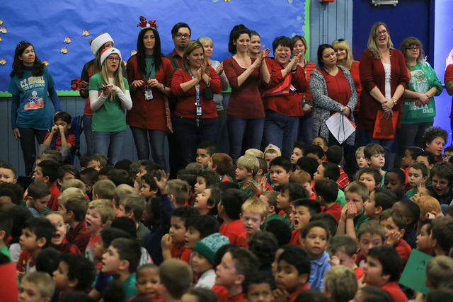 Faculty members applaud students before the students receive gifts at C.T. Sewell Elementary School in Henderson on Friday, Dec. 16, 2016. The gifts were donated by Bob and Sandy Ellis, who have d ...