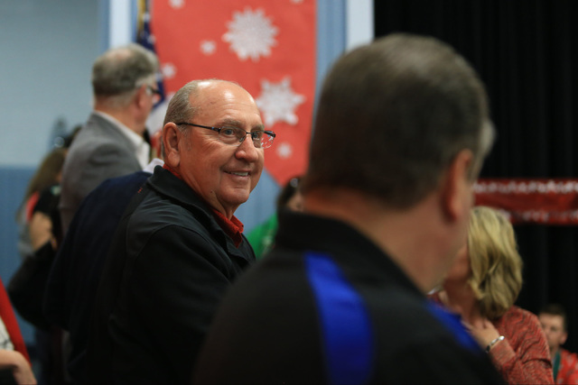 Bob Ellis watches students before they receive gifts at C.T. Sewell Elementary School in Henderson on Friday, Dec. 16, 2016. The gifts were donated by Bob and Sandy Ellis, who have donated more th ...