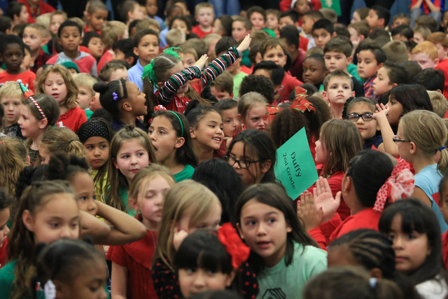 A young girl dabs as Santa talks to students before giving them gifts at C.T. Sewell Elementary School in Henderson on Friday, Dec. 16, 2016. The gifts were donated by Bob and Sandy Ellis, who hav ...