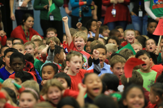 Students at C.T. Sewell Elementary School in Henderson cheer for the arrival of Santa on Friday, Dec. 16, 2016. The gifts were donated by Bob and Sandy Ellis, who have donated more than 20,000 sho ...