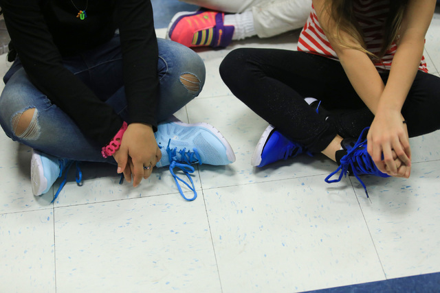 Students wear new shoes while listening to Santa speak at C.T. Sewell Elementary School in Henderson on Friday, Dec. 16, 2016. Gifts for every student at the school were donated by Bob and Sandy E ...