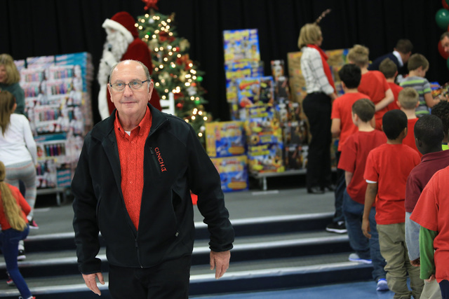 Bob Ellis watches walks between students as they line up to receive gifts at C.T. Sewell Elementary School in Henderson on Friday, Dec. 16, 2016. The gifts were donated by Bob and Sandy Ellis, who ...