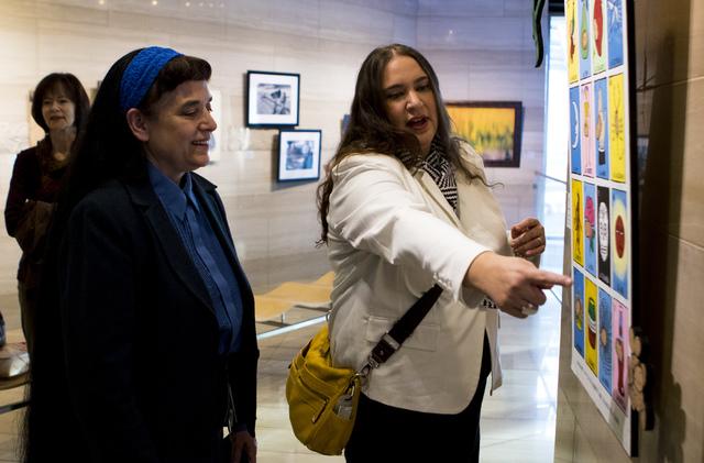 Sandra Margarita Ward Craig, right, shows off her art during a city employee art exhibit at Las Vegas City Hall on Thursday, Dec. 8, 2016. (Miranda Alam/Las Vegas Review-Journal) @miranda_alam