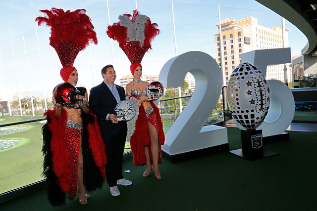 Las Vegas Bowl executive director John Saccenti with Las Vegas showgirls, Jennifer Gagliano, left and Jennifer Autry, right, during a news conference regarding the Las Vegas Bowl at Topgolf Las Ve ...