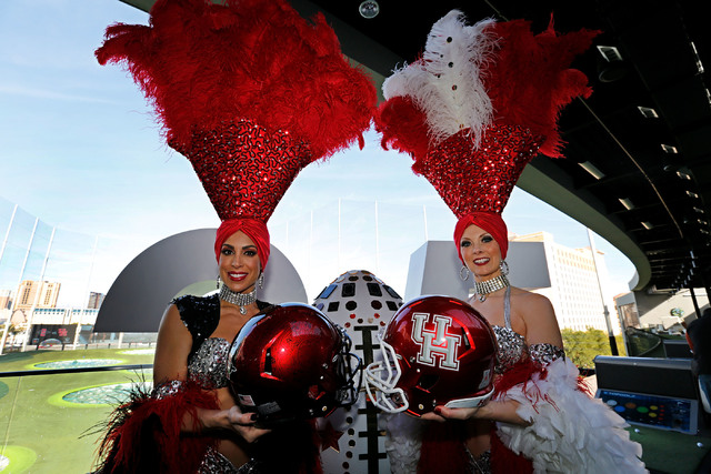 Las Vegas showgirls, Jennifer Gagliano, left,  holding a helmet of SanDiego State University and Jennifer Autry holding a helmet of University of Huston during a news conference regarding the Las  ...