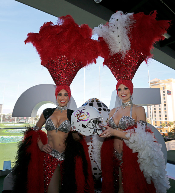 Las Vegas showgirls, Jennifer Gagliano, left, and Jennifer Autry holding a helmet that celebrates the Las Vegas Bowl's 25th anniversary milestone during a news conference regarding the Las Vegas B ...