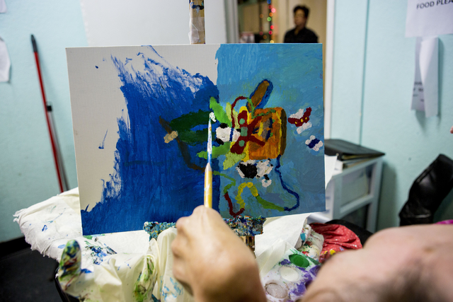 Kai Schaffer, an individual at Transition Services facility with cerebral palsy, paints a detailed work of art at the facility in Henderson, Thursday, Dec. 15, 2016. Schaffer paints daily and sell ...