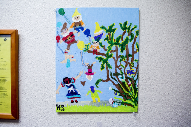 A painting created by Kai Schaffer, an individual at Transition Services facility with cerebral palsy, hangs on the wall at the facility in Henderson, Thursday, Dec. 15, 2016. Schaffer paints dail ...