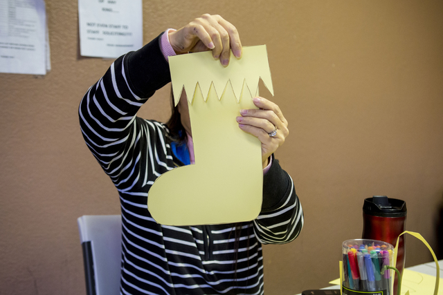 Anne Church, an individual at Transition Services facility, constructs a paper stocking for decorations to hang around the facility in Henderson, Thursday, Dec. 15, 2016. (Elizabeth Page Brumley/L ...