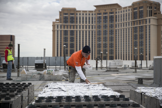 Pyrotechnician Henry Herman works on the electrical wiring of fireworks for the New Year's Eve firework show on the roof of the Treasure Island hotel-casino on Friday, Dec. 30, 2016, in Las ...