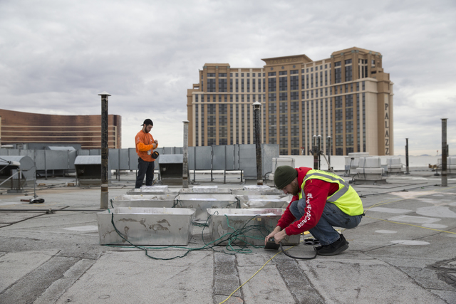 Pyrotechnician Kale Hamel, right, works on the electrical wiring of fireworks for the New Year's Eve firework show on the roof of the Treasure Island hotel-casino on Friday, Dec. 30, 2016,  ...