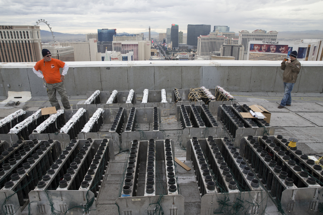 Pyrotechnician Henry Herman, left, works on the electrical wiring of fireworks for the New Year's Eve firework show on the roof of the Treasure Island hotel-casino on Friday, Dec. 30, 2016, ...