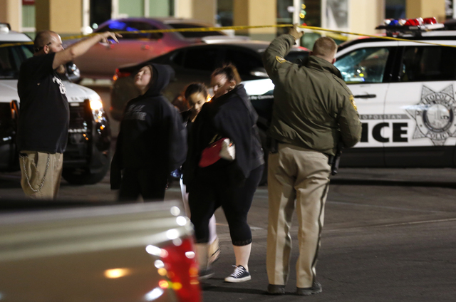 Las Vegas police officers escort three people out of a fatal shooting scene at 8665 W. Flamingo Road on Friday, Dec. 2, 2016. A young teen died after a store clerk shot him in the head during an a ...