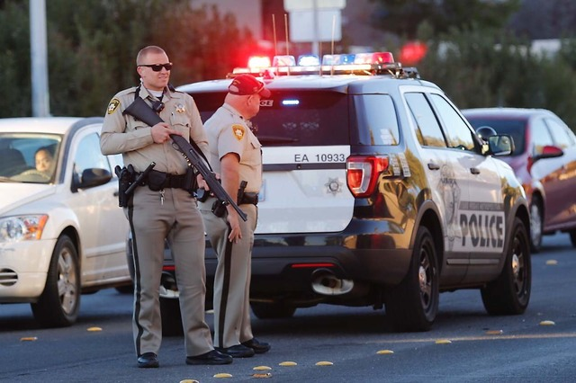 Police officers stand on a street near West Flamingo Animal Hospital in Las Vegas, Monday, Dec. 19, 2016 after a shooting.  (Chitose Suzuki/LasVegas Review-Journal)