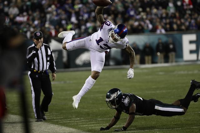 New York Giants' Odell Beckham (13) is hit by Philadelphia Eagles' Leodis McKelvin (21) during the second half of an NFL football game, Thursday, Dec. 22, 2016, in Philadelphia. (AP Photo/Michael  ...