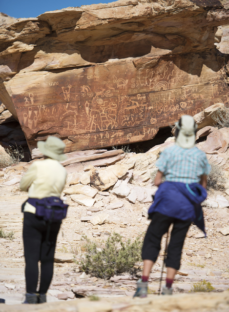 "Hikers check out ""Newspaper Rock"" in the Falling Man petroglyph area in the Gold Butte region Saturday, Oct. 15, 2016, northeast of Las Vegas. Sam Morris/Las Vegas News Bureau"