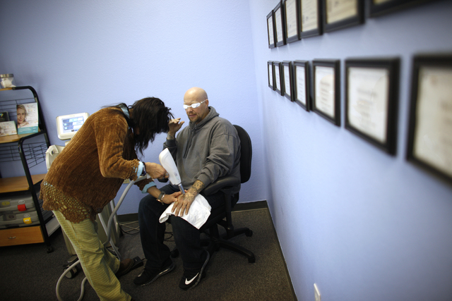 Robyn Grace laser removes the tattoos of ex-offender Marty Byars at her office on Sunday, Dec. 11, 2016, in Las Vegas. Grace is the founder of A Doors Open, a laser tattoo removal non-profit that  ...