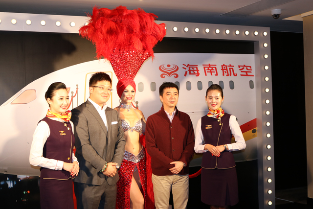 Hainan Airlines flight attendants April Lu, left, and Lavin Yuan pose with Wang Yi Bin, left, and Chen Qing Long, as well as with Las Vegas showgirl Laura during a launch party for Hainan Airlines ...