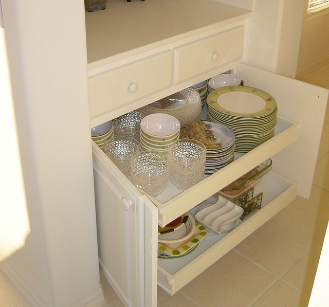 COURTESY EZ ROLL-OUT DRAWERS These roll-out cabinet shelves are a handy place to store party plates an